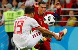 Portugal's forward Cristiano Ronaldo (R) vies for the ball with Iran's defender Majid Hosseini during the Russia 2018 World Cup Group B football match between Iran and Portugal at the Mordovia Arena in Saransk on June 25, 2018. PHOTO: AFP