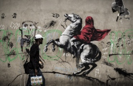 A man walks past a recent artwork by street artist Banksy in Paris on June 25, 2018. Anonymous street artist Banksy's artwork of Napoleon Bonaparte wearing a headscarf inspired by the original painting by Jacques-Louis David has been found, in northern Paris over the weekend.  / AFP PHOTO / Philippe LOPEZ /