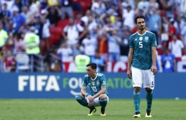 Germany's defender Mats Hummels (R) and Germany's midfielder Mesut Ozil react to their defeat during the Russia 2018 World Cup Group F football match between South Korea and Germany at the Kazan Arena in Kazan on June 27, 2018. / AFP PHOTO / BENJAMIN CREMEL /