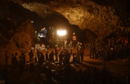 Thai soldiers relay electric cable deep into the Tham Luang cave at the Khun Nam Nang Non Forest Park in Chiang Rai on June 26, 2018 during a rescue operation for a missing children's football team and their coach.  Desperate parents led a prayer ceremony outside a flooded cave in northern Thailand where 12 children and their football coach have been trapped for days, as military rescue divers packing food rations resumed their search on June 26. / AFP PHOTO / Lillian SUWANRUMPHA