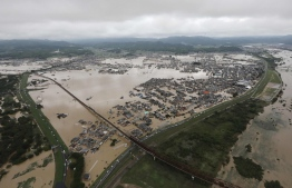 """This picture shows an aerial view of flooded houses in Kurashiki, Okayama prefecture on July 8, 2018. Japan's Prime Minister Shinzo Abe warned of a """"race against time"""" to rescue flood victims as authorities issued new alerts over record rains that have killed at least 48 people. / AFP PHOTO / JIJI PRESS / STR /"""