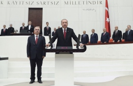 This hand out picture taken and released on July 9, 2018 by Turkish President Office shows Turkish President Recep Tayyip Erdogan speaking at the Grand National Assembly of Turkey (TBMM) to take oath of office in Ankara.  Erdogan was sworn in for his second term as head of state on July 9, taking on greater powers than any Turkish leader for decades under a new system condemned by opponents as a one-man regime. Erdogan, who has transformed Turkey in 15 years of rule by allowing Islam a greater role in public life and boosting its international stature, took his oath in parliament for a five-year term after his June election victory.  / AFP PHOTO / Turkish President Office / KAYHAN OZER /