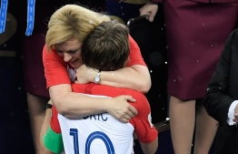 Croatian President Kolinda Grabar-Kitarovic (rear C) comforts Croatia's midfielder Luka Modric (front C) during the trophy ceremony at the end of the Russia 2018 World Cup final football match between France and Croatia at the Luzhniki Stadium in Moscow on July 15, 2018. / AFP PHOTO / GABRIEL BOUYS /