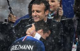 French President Emmanuel Macron (R) congratulates France's forward Antoine Griezmann during the trophy ceremony after winning the Russia 2018 World Cup final football match between France and Croatia at the Luzhniki Stadium in Moscow on July 15, 2018. / AFP PHOTO / FRANCK FIFE /