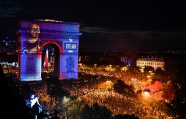 This picture taken from the terrace of the Publicis drugstore  on July 15, 2018 shows a portrait of French forward Kylian Mbappe projected on Paris' landmark Arc de Triomphe as people gather to celebrate France's victory in the Russia 2018 World Cup final football match between France and Croatia, on the Champs-Elysees avenue in Paris.  / AFP PHOTO / GERARD JULIEN