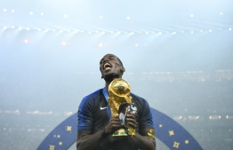 France's midfielder Paul Pogba celebrates with the World Cup trophy after the Russia 2018 World Cup final football match between France and Croatia at the Luzhniki Stadium in Moscow on July 15, 2018. / AFP PHOTO / FRANCK FIFE /