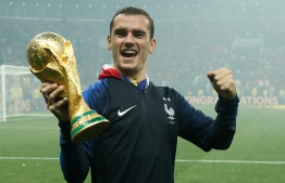 France's forward Antoine Griezmann celebrates with the World Cup trophy after the Russia 2018 World Cup final football match between France and Croatia at the Luzhniki Stadium in Moscow on July 15, 2018. / AFP PHOTO / Odd ANDERSEN /
