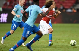 """(FILES) In this file photo taken on July 26, 2018, Arsenal's Matteo Guendouzi (R) runs with the ball past Atletico Madrid's players during their International Champions Cup football match in Singapore. French whizz Matteo Guendouzi said he hopes he's embarking on a """"big adventure"""" with Arsenal after a scintillating start which has drawn comparisons with the great Patrick Vieira. / AFP PHOTO / Roslan RAHMAN"""