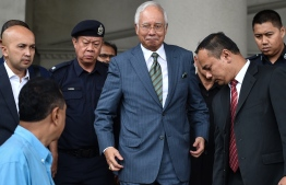 Malaysia's former prime minister Najib Razak (C) leaves Duta court complex in Kuala Lumpur on August 8, 2018. Malaysia's former prime minister Najib Razak was hit with new charges on August 8 linked to a multi-billion-dollar financial scandal that contributed to his shock election defeat in May. / AFP PHOTO / Mohd RASFAN
