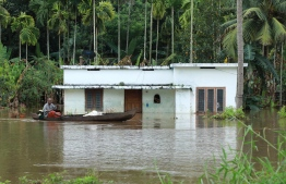 An Indian man rides his boat next to houses immersed in flood waters in Ernakulam district of Kochi, in the Indian state of Kerala on August 10, 2018. Flash floods have claimed at least 27 lives in the southern Indian state of Kerala, officials said on August 10, prompting the US to advise its citizens to stay away from the tourist hotspot. / AFP PHOTO / -