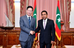 Chinese ambassador to the Maldives Zhang Lizhong (L) shakes hands with President Abdulla Yameen (R) at the President's. - PHOTO: President's Office