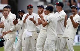England's players react to the result of the review for the wicket of India's captain Virat Kohli during play on the fourth day of the second Test cricket match between England and India at Lord's Cricket Ground in London on August 12, 2018. / AFP PHOTO / Adrian DENNIS /