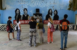 This picture taken on June 18, 2018 shows tourists taking pictures of a mural at the now-derelict ashram visited by the Beatles 50 years ago, in Rishikesh in northern India.  Fifty years after the Beatles came to India, the bungalows where the Fab Four lived, the post office where John Lennon sent Yoko Ono postcards and the giggling guru's house are all ruins. / AFP PHOTO / Sajjad HUSSAIN