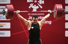 Sohrab Moradi of Iran performs a lift to break the world record in the men's 94kg class  weightlifting event at the 2018 Asian Games in Jakarta on August 25, 2018. / AFP PHOTO / Bay ISMOYO