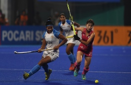 Japan's Minami Shimizu (R) and India's Deepika fight for the ball during the women's field hockey final match between India and Japan at the 2018 Asian Games in Jakarta on August 31, 2018.  AAMIR QURESHI / AFP