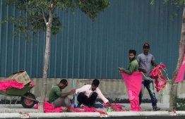 Expatriate workers working to hang up flags of PPM. PHOTO: SOCIAL MEDIA