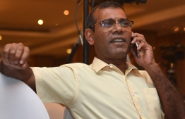 Former President of the Maldives Mohamed Nasheed speaks on the phone at a hotel in Colombo on September 23, 2018 as his candidate Ibrahim Mohamed Solih was set to win. The Maldives' opposition leader was ahead in early counting for today's controversial election by a large margin, local media said, after a campaign marred by police raids on the opposition and allegations of rigging in favour of strongman President Abdulla Yameen. / AFP PHOTO / LAKRUWAN WANNIARACHCHI