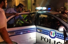 A police officer leads an arrested individual into a police vehicle. FILE PHOTO/MIHAARU