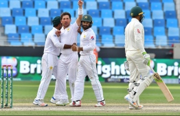 Pakistan batsman Yasir Shah (2L) celebrates after dismissing Australian cricketer Usman Khawaja during day five of the first Test cricket match in the series between Australia and Pakistan at the Dubai International Stadium in Dubai on October 11, 2018. (Photo by GIUSEPPE CACACE / AFP)