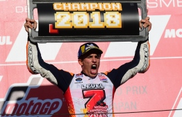 Repsol Honda Team Spanish rider Marc Marquez celebrates on the podium of the MotoGP Japanese Grand Prix at Twin Ring Motegi circuit in Motegi, Tochigi prefecture on October 21, 2018. - Honda's Marc Marquez stormed to victory in a nail-biting Japan race on October 21 to capture his third straight MotoGP world title. (Photo by Martin BUREAU / AFP)