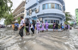 People wade across flooded streets after heavy monsoon showers in capital Male City. PHOTO: NISHAN ALI/MIHAARU