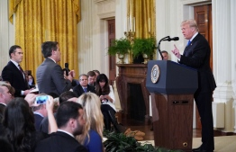 US President Donald Trump (R) gets into a heated exchange with CNN chief White House correspondent Jim Acosta (C) as NBC correspondent Peter Alexander (L) looks on during a post-election press conference in the East Room of the White House in Washington, DC on November 7, 2018. (Photo by MANDEL NGAN / AFP)