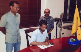 Former President Mohamed Nasheed (L) watches on as Ihavandhoo MP Mohamed Abdulla signs document to join MDP. PHOTO/MDP