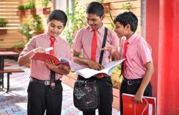 Three students enrolled at Iskandhar School examine their report cards. PHOTO: NISHAN ALI / MIHAARU