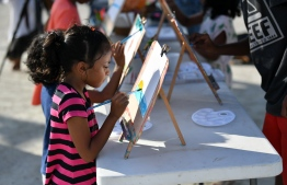 A kid drawing a sunrise at the 'Arty Fingers' stall during the 5-year anniversary show of 'Fannuge Dharin'. PHOTO: AHMED NISHAATH/MIHAARU