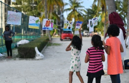 Kids looking at the paintings and drawings made at the 'Arty Fingers' stall during the 5-year anniversary show of 'Fannuge Dharin'. PHOTO: AHMED NISHAATH/MIHAARU
