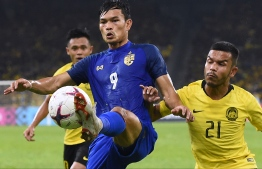Thailand's forward Adisak Kraisorn (C) and Malaysia's defender Nazirul Naim Che Hashim fight for the ball during the first leg of the AFF Suzuki Cup 2018 semifinal football match between Malaysia and Thailand at the Bukit Jalil National Stadium in Kuala Lumpur on December 1, 2018. (Photo by MOHD RASFAN / AFP)
