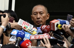 """Film director Doze Niu (C), also known as Niu Chen-zer, is surrounded by the press outside a police station in Taipei on December 7, 2018. - Acclaimed Taiwanese director Doze Niu has been accused of sexually assaulting a female crew member working on his latest film, """"Pao Ma"""". Niu, who appeared at a Taipei police station for questioning on December 7, said he would cooperate with the investigation. (Photo by Sam YEH / AFP)"""