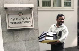 Nazim Sattar entering the premises of the President's Office with documents pertaining to the cases. PHOTO: MIHAARU