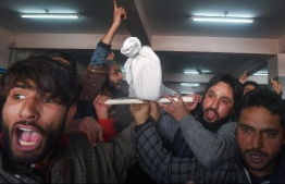 Kashmiris shout slogans as they carry away the shrouded body of a youth, killed during clashes with authorities, at the main hospital in Srinagar on December 15, 2018. - Seven civilians, three armed rebels and a soldier were killed on December 15 during a gunfight and clashes with protestors in Indian-administered Kashmir, police and hospital authorities said. (Photo by TAUSEEF MUSTAFA / AFP)