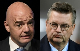 (COMBO) This combination of pictures created on December 19, 2018 shows FIFA president Gianni Infantino (L, during the 68th Conmebol Council meeting in Buenos Aires, Argentina, on April 12, 2018) and Reinhard Grindel, President of the German Football Federation (Deutscher Fussball Bund, DFB, prior the FIFA World Cup 2018 qualification football match between Germany and Azerbaijan in Kaiserslautern, western Germany, on October 8, 2017). - German Football Federation president Reinhard Grindel has launched a withering attack on FIFA president Gianni Infantino over a lack of transparency on proposals for new competitions in an interview with Sportbuzzer.de published on Wednesday, December 19, 2018. (Photos by EITAN ABRAMOVICH and Christof STACHE / AFP)