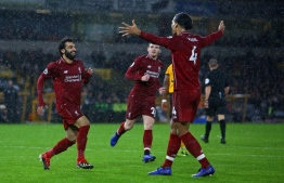 Liverpool's Egyptian midfielder Mohamed Salah (L) runs to leap into the arms of Liverpool's Dutch defender Virgil van Dijk as he celebrates after scoring the opening goal of the English Premier League football match between Wolverhampton Wanderers and Liverpool at the Molineux stadium in Wolverhampton, central England  on December 21, 2018. (Photo by Geoff CADDICK / AFP) / RESTRICTED TO EDITORIAL USE. No use with unauthorized audio, video, data, fixture lists, club/league logos or 'live' services. Online in-match use limited to 120 images. An additional 40 images may be used in extra time. No video emulation. Social media in-match use limited to 120 images. An additional 40 images may be used in extra time. No use in betting publications, games or single club/league/player publications. /