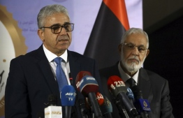 "Libyan Foreign Minister Mohamed Taher Siala (R) and Interior Minister Fathi Bash Agha (L) deliver a speech on December 25, 2018, following an attack on the Foreign ministry. - Suicide attackers stormed the Libyan foreign ministry in the capital Tripoli, killing at least three people including a senior civil servant, the authorities said. Ten other people were wounded in what the foreign ministry said was a suicide attack carried out by ""terrorists"". (Photo by Mahmud TURKIA / AFP)"