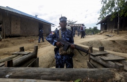 "A Myanmar border guard policeman gurads a police station in Buthidaung on January 7, 2019. - Myanmar has called on its military to ""launch operations"" against ethnic Rakhine rebels behind a deadly attack on four police stations last week, a government spokesman said on January 7, as a surge of violence grips the restive western state. (Photo by - / AFP)"