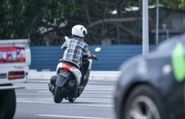 A man driving around Capital City Male with a helmet on. PHOTO: HUSSAIN WAHEED/MIHAARU