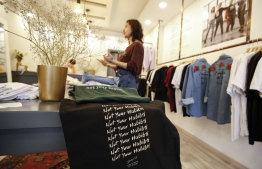 """Palestinian fashion designer Yasmeen Mjalli speaks while standing in her clothing shop where her label collection """"BabyFist"""" carrying anti-sexual harassment slogans is showcased, in Ramallah in the occupied West Bank on December 19, 2018. - It's only three words on a T-shirt or embroidered on a denim jacket, but they carry a powerful message: """"Not you habibti (darling)."""" """"BabyFist"""" label founder Yasmeen Mjalli, 22, sees the clothes helping to empower Palestinian women facing unwelcome male attention in public, placing on the fabrics of muted colours and on canvas bags messages in English and Arabic inside drawings of flowers and other designs. (Photo by ABBAS MOMANI / AFP)"""