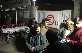 Afghan relatives and medical staff wait for victims outside an entrance gate of the Emergency Hospital after a car bomb exploded near a foreign compound, in Kabul on  January 15, 2018. - A car bomb exploded near a foreign compound in the east of Kabul on Janaury 14, wounding more than 40 people, officials said, in the latest attack to rock the Afghan capital. There was no immediate claim of responsibility for the attack, but interior ministry spokesman Najib Danish said the blast had targeted Green Village, where some foreign workers are based. (Photo by Wakil KOHSAR / AFP)