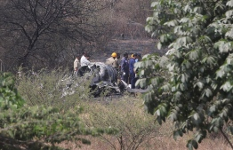 Indian officials gather around the remains of an Indian Air Force Mirage 2000 aircraft that crashed minutes after take-off in Bangalore on February 1, 2019, killing the two pilots. - The single-engine jet fighter aircraft manufactured by Dassault Aviation was on a test flight after an upgrade carried out by India's Hindustan Aeronautics Limited (HAL). (Photo by STR / AFP)