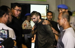Frenchman Felix Dorfin (C) is under escort after escaping from jail in Mataram on the holiday island of Lombok on February 2, 2019, helped by a police officer who received 1,000 USD bribe from him. - A French drug suspect, who has been on the run in Indonesia for about 10 days, has been recaptured by the police. Dorfin was found in Pusuk forest in North Lombok late on February 1, police said, and was immediately taken back to the police jail in Lombok's capital Mataram. (Photo by PIKONG / AFP)