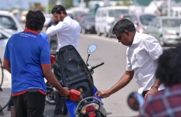 A motorcycle being refuelled at a petrol shed. PHOTO: HUSSAIN WAHEED/ MIHAARU