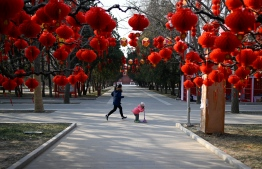 A girl runs with a child standing a scooter past red lanterns ahead of the Chinese Lunar New Year at a park in Beijing on January 24, 2019. (Photo by WANG ZHAO / AFP)