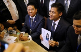 An official of Raksa Chart party holds the registration document bearing the photograph of Thai Princess Ubolratana prior to submitting to election commission officials in Bangkok on February 8, 2019. - Thai Princess Ubolratana will run for prime minister in upcoming elections with a party tied to the divisive Shinawatra political family, an official said February 8, a shock twist that deals a blow to the ruling junta's hopes of holding onto power. (Photo by Krit Phromsakla Na SAKOLNAKORN / THAI NEWS PIX / AFP)