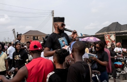 Modern Democratic Party (MDP) candidate US-Nigerian musician Olubankole Wellington popularly known as Banky W. speaks to supporters during a campaign rally at Ajah in Lagos, on January 27, 2019. - Banky W. was born in the United States to Nigerian parents -- an engineer father and church pastor mother. Banky W. hopes to win a seat in the House of Representatives for the Modern Democratic Party (MDP), which was only created last year. The party's platform includes introducing free and compulsory primary education in a country where an estimated 13 million children do not go to school and the creation of vocational training centres to equip people with employable skills. (Photo by FLORIAN PLAUCHEUR / AFP)