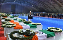 This handout photograph taken and released by India's Press Information Bureau (PIB) on February 15, 2019 shows Indian Prime Minister Narendra Modi gesturing as he walks next to coffins with the bodies of Indian troops killed in an attack in Kashmir, at Palam airport in New Delhi. - India and Pakistan's troubled ties risked taking a dangerous new turn as New Delhi accused Islamabad of harbouring militants behind one of the deadliest attacks in three decades of bloodshed in Indian-administered Kashmir. (Photo by Handout / PIB / AFP) /