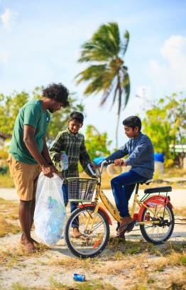 Shameel from Stand Up For Our Seas team cleans up Thulhaadhoo with local little ones. PHOTO: JAMES APPLETON PHOTOGRAPHY / STAND UP FOR OUR SEAS.