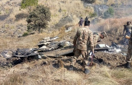 Pakistani soldiers stand next to what Pakistan says is the wreckage of an Indian fighter jet shot down in Pakistan controled Kashmir at Somani area in Bhimbar district near the Line of Control on February 27, 2019. - Pakistan and India said on Febraury 27 they had shot down each other's warplanes, in a dramatically escalating confrontation that has fuelled concerns of an all-out conflict between the nuclear-armed rivals. (Photo by STR / AFP)